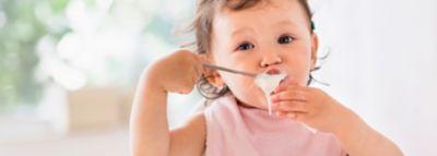 Ein Baby isst Babynahrung aus einer Schüssel und benutzt dabei einen Löffel.