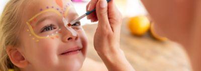 Kinderschminke: Ein kleines Mädchen bekommt einen Schmetterling ins Gesicht gemalt.