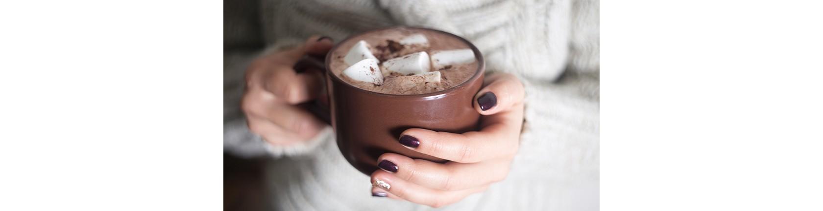 Weibliche Hand hält eine große Tasse Kakao mit Marshmallows.