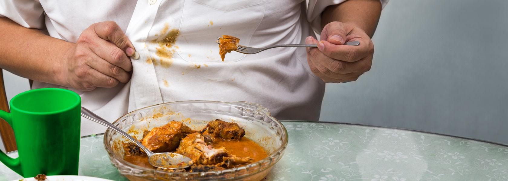 Mehrere Kochlöffel voll mit unterschiedlichen Gewürzen wie Curry liegen hübsch drappiert auf einem runden Tablett aus Marmor.