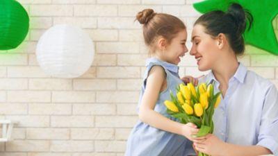 Mutter und Tochter in heller Kleidung sitzen lächelnd auf Bett mit weißem Bezug und halten einen Strauß gelber Tulpen in Händen