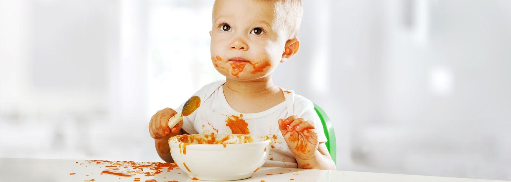 Baby in weißem Kurzarmbody voll mit orangefarbenen Breiflecken auf Kleidung, Mund und Händen isst Brei aus weißer Schale
