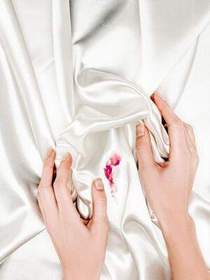 Frau enhände halten weißes Seidentuch mit rotem Fleck