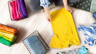 Frau sitzt auf dem Boden und legt ein gelbes T Shirt zusammen, daneben stehen Drahtkörbe mit gefalteter bunter Kleidung