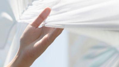 Frauenhand vor hellem Hintergrund hält weißes Kleidungsstück
