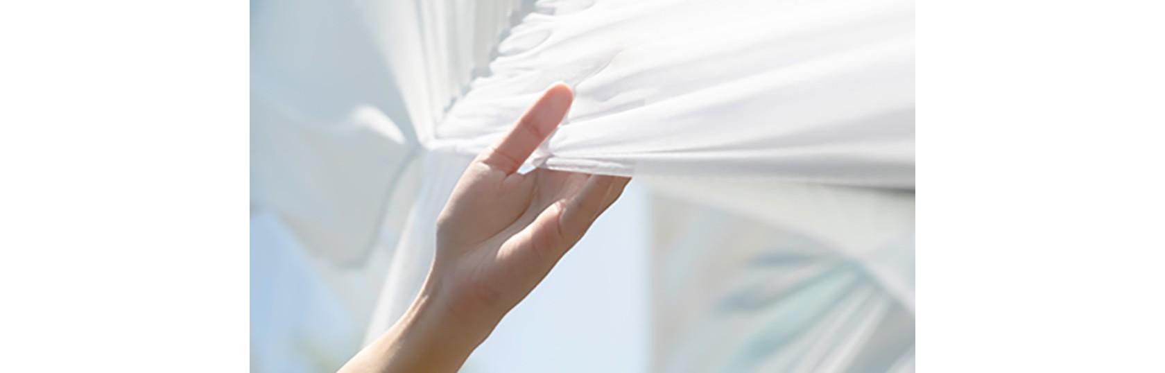 Frischgewaschene weiße Kleidung hängt in der Abenddämmerung an der Wäscheleine im Garten.