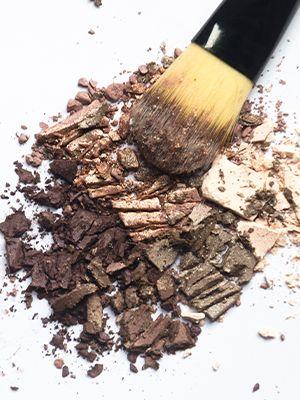 Ein Kosmetikpinsel liegt auf zerbrochenem glitzerndem Lidschatten.