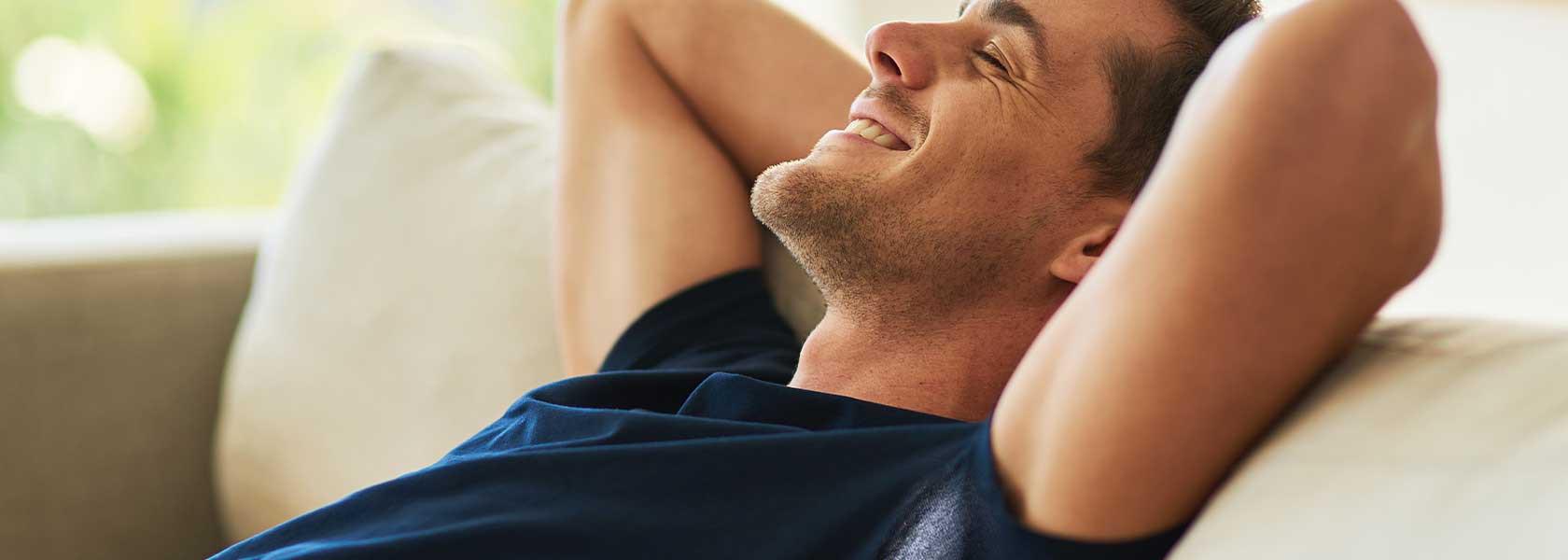 Ein Mann auf der Couch benutzt seine Hände als Kopfstütze, unter seiner Achsel ein weißer Deodorant-Fleck.