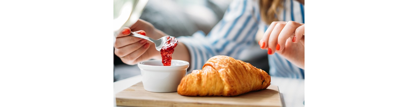 Eine Frau ist im Begriff,  Früchtegelee auf ihr Croissant zu schmieren - der Fokus liegt auf ihren Händen.