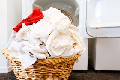 Πλεκτό καλάθι γεμάτο λευκά ρούχα και ένα κόκκινο ρούχο.