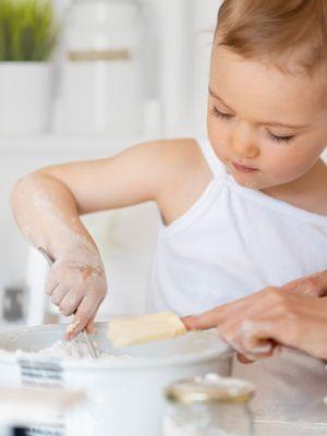 Mutter und Kind backen einen Kuchen, das kleine Kind rührt, während seine Mutter ein Stück Butter in die Schüssel gibt.