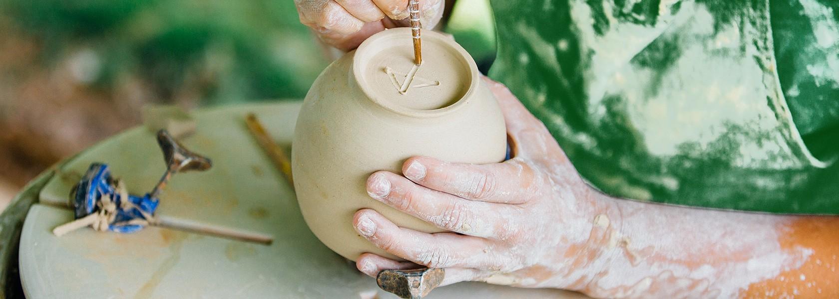 person mit tonflecken an den händen bearbeitet tongefäß