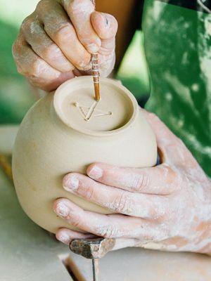 Nahansicht von Händen eines Mannes in schmutziger Schürze, der mit Ton töpfert