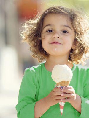 Kleines brünettes Mädchen in grünem Shirt isst draußen Eis.
