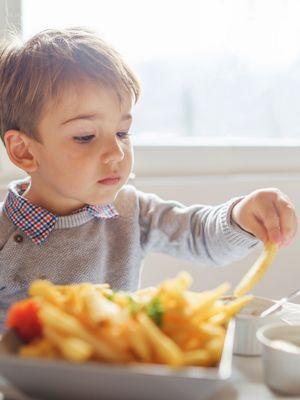 Kleiner brünetter Junge isst Pommes mit Mayonnaise.