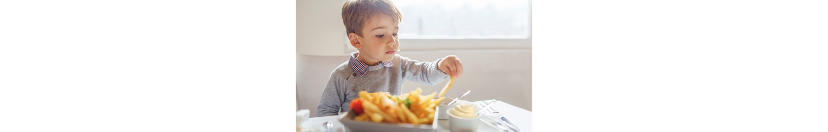 junge mit grauem pullover sitzt am tisch und isst pommes