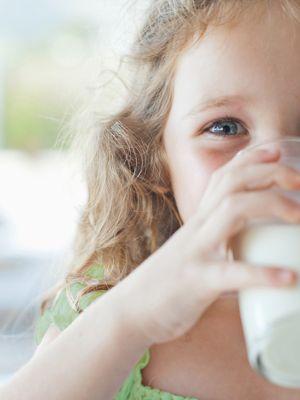 Ein kleines blondes Mädchen trinkt ein Glas Milch.