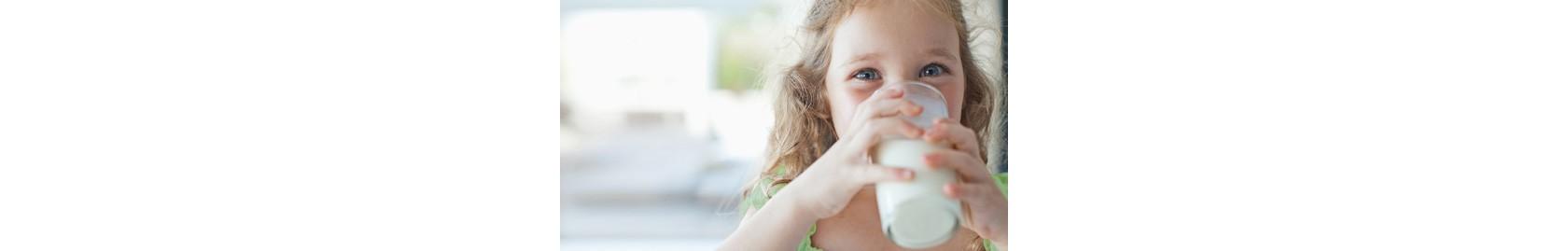 mädchen trinkt lächelnd aus milchglas