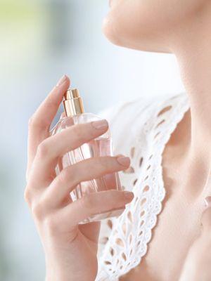 Brünette Frau sprüht sich Parfüm auf den Hals.