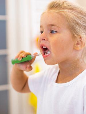 Kleines blondes Mädchen beim Zähneputzen