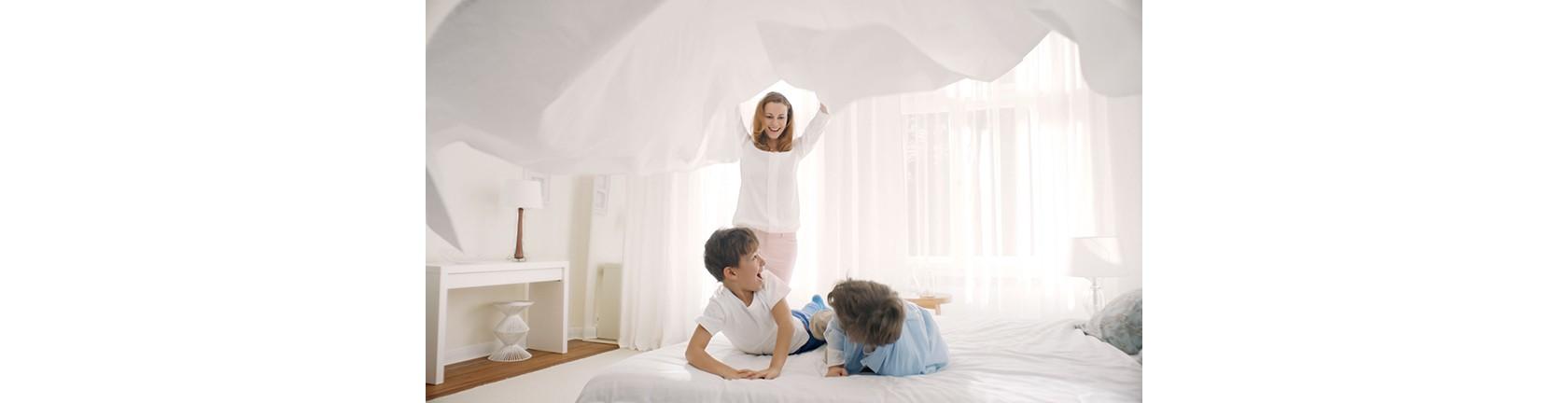 Zwei kleine Jungs tollen fröhlich auf dem Bett herum, ihre Mutter ist gerade im Begriff, sie mit einem strahlend weißen Lacken zuzudecken.