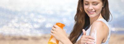 Μια νεαρή γυναίακα βάζει αντηλιακό στο χέρι της