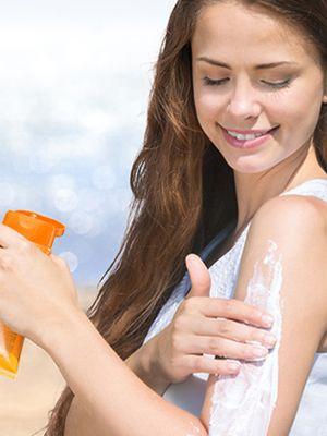 Eine junge Frau trägt sich Sonnencreme auf ihren Oberarm auf.