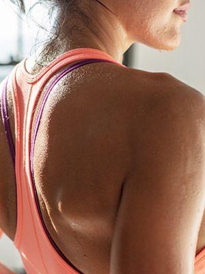 Hrbtni pogled na žensko v športni opremi in kapjice pota na njeni koži.