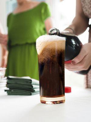 Frau gießt Cola in überlaufendes Glas auf einem Tisch