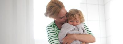 mutter hält lachendes kleinkind in grauem handtuch im arm
