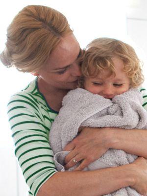 Mutter umarmt ihr Kleinkind, das in ein frisches Handtuch gewickelt ist.