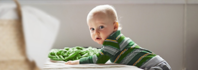 baby liegt auf bett mit babywäsche