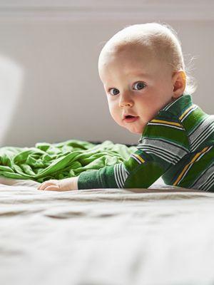 Blondes Baby liegt in einem grün-gestreiften Longsleeve und einer grauen Hose auf einem Bett.