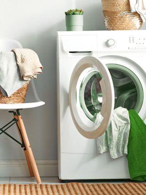 Geflochtener Korb mit schmutziger Wäsche steht auf einem weißen Stuhl neben einer Waschmaschine, die ebenfalls bereits mit etwas Wäsche beladen ist