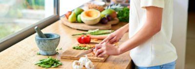 Frau in weißem T Shirt schneidet Gemüse in der Küche