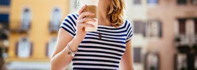 Blonde Frau in einem blau weiß gestreiften T-Shirt mit Kaffeefleck hält Kaffeebecher in der Hand