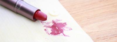 Roter Lippenstift liegt auf Tuch mit Lippenstiftfleck