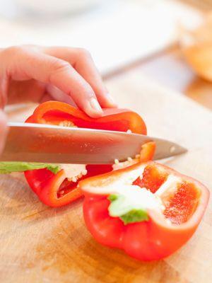 Person schneidet mit einem Messer rote Paprika auf einem Holzbrett