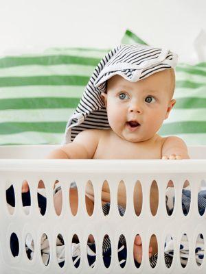Ein kleines Baby sitzt in einem Wäschekorb mit frischer Wäsche und hat einen Strampler auf dem Kopf.