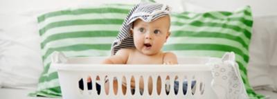 baby sitzt in wäschekorb mit babykleidung