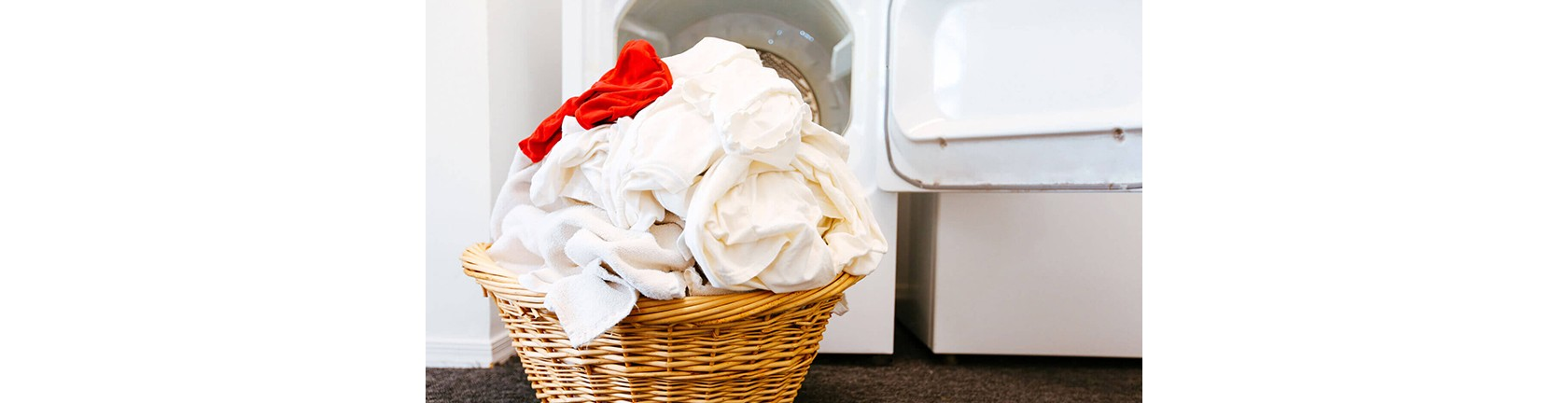 Geflochtener Korb voll mit weißer Wäsche und einem roten Kleidungsstück.