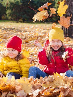 mädchen mit roter daunenjacke und mädchen mit gelber  daunenjacke spielen auf wiese mit  trockenen laub