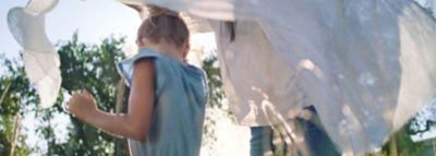 Ein Mädchen schlängelt sich zwischen an der Leine hängenden Wäsche durch.