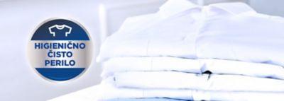 "Zložene sveže srajce, poleg nalepka z napisom ""higienično čisto perilo""."