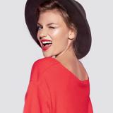 Eine Frau mit einem roten Oberteil und schwarzen Hut dreht sich zur Kamera und zwinkert