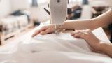 Eine Nahaufnahme einer Person an einer Nähmaschine – das Reparieren von Kleidungsstücken ist eine Möglichkeit, die Lebensdauer zu verlängern und Slow Fashion zu unterstützen