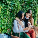Zwei Frauen sitzen vor einer bepflanzten Wand, sie schauen auf ein Handy und lächeln dabei