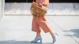 Unterkörperansicht einer Frau mit orangener Hose und hellblauen Schuhen auf der Straße