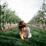 Sicht von hinten auf eine Frau,die auf einer Wiese liegt, links und rechts stehen kleine Bäume in Reihe