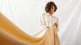 Eine Frau steht vor einem weißen Stoffhintergrund, sie zieht an einem gelben Stoff im Vordergrund